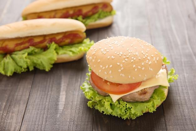 Hot dogi i hamburgery na drewnianym tle