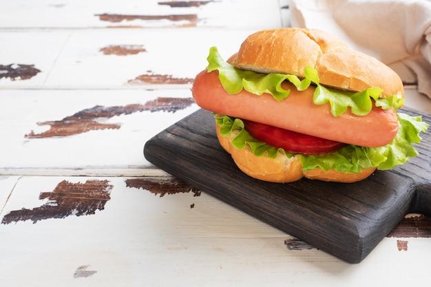 Hot dogi na drewnianej desce. hot dog z sałatą, pomidorem i kiełbasą. skopiuj miejsce
