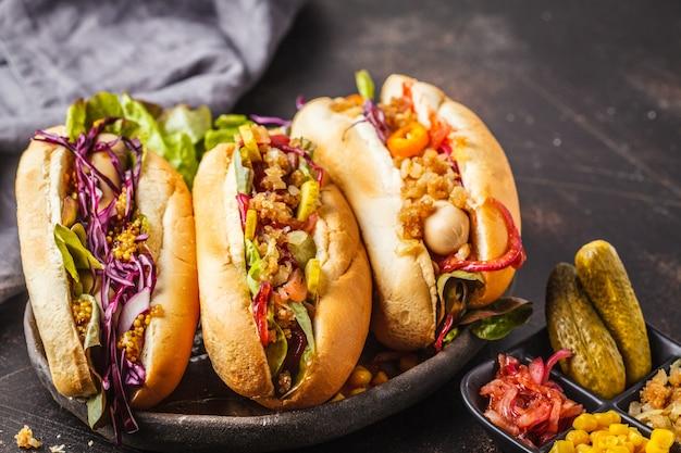 Hot dogi z asortowanymi polewami na ciemnym tle, odgórny widok.