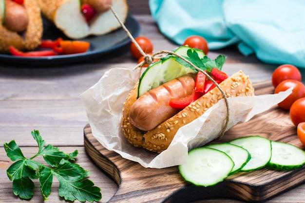 Hot dogi z bułeczkami sezamowymi i świeżymi warzywami na talerzu na drewnianym stole