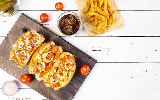 Hot dogi z warzywami, musztardą i keczupem na desce do krojenia na białym drewnianym stole, widok z góry, copyspace
