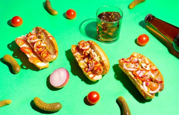 Hot dogi z warzywami, musztardą i keczupem na jasnozielonym tle