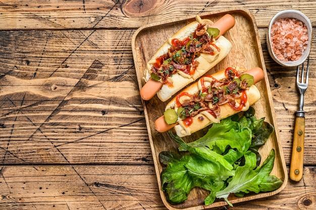 Hot dogi ze smażonym boczkiem, cebulą i ogórkami kiszonymi.