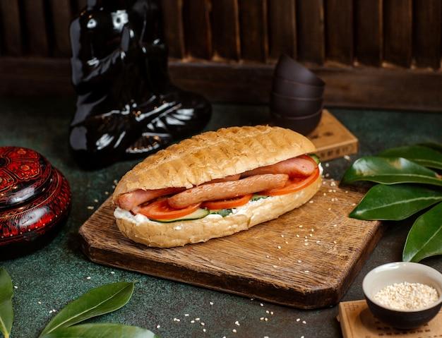 Hotdog chleb faszerowany kiełbasami, pomidorami, ogórkiem i majonezem