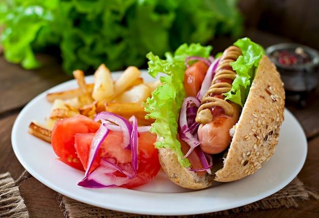 Hotdog z musztardą keczup i sałatą na drewnianym stole.