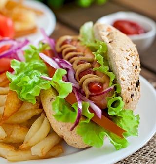 Hotdog z musztardą keczupową i sałatą na drewnianej powierzchni.
