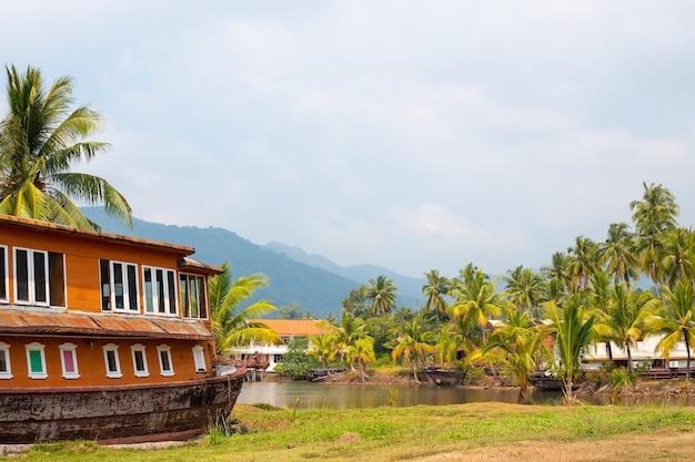 Hotel w kształcie statku w tropikach, wśród palm kokosowych i rzeki