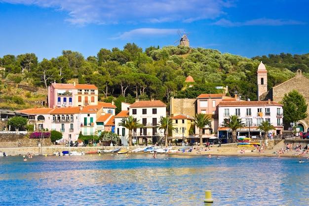 Hotele przy plaży w miejscowości collioure z wiatrakiem na szczycie wzgórza, roussillon, wybrzeże vermilion, pireneje wschodnie, francja