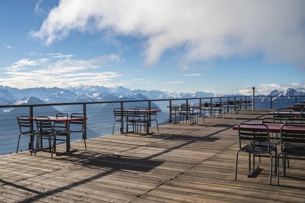 Hotelowy balkon ze stołami i krzesłami z widokiem na otaczające alpy i jeziora w pochmurny dzień