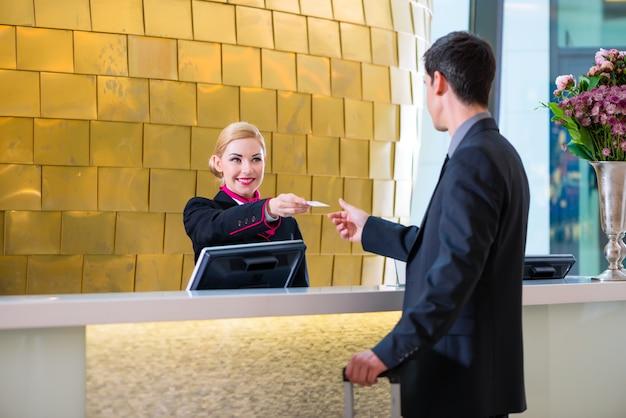 Hotelowy recepcjonista sprawdza w mężczyzna daje kluczowej karcie