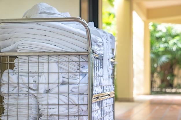 Hotelowy wózek pokojowy parkingowy przed pokojem z czystym ręcznikiem i szlafrokami gotowymi do zmiany i uzupełnienia pokoju.