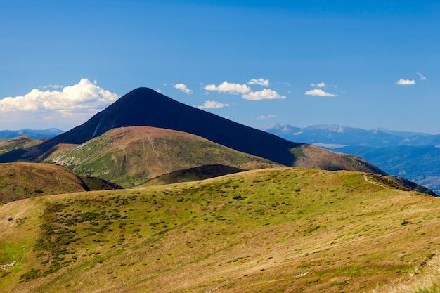 Hoverla w karpatach na ukrainie. piękny widok górski w lecie z zieloną łąką i niebieskim niebem.