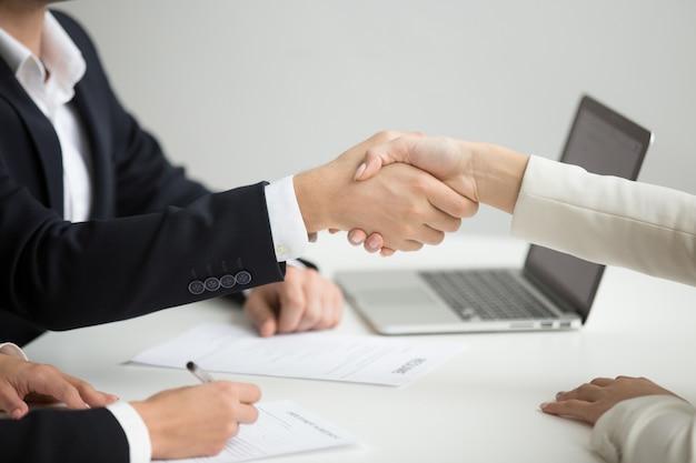 Hr handshaking pomyślny kandydat dostaje pracującego przy nową pracą, zbliżenie