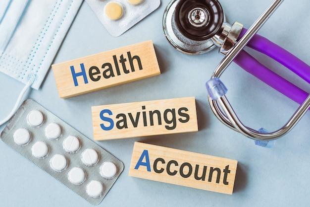 """Hsa, symbol konta oszczędnościowego zdrowia. drewniane kostki z napisem """"hsa, zdrowotne konto oszczędnościowe""""."""