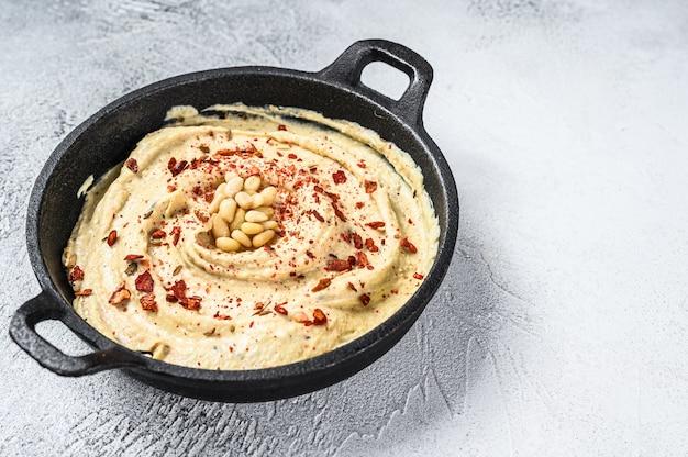 Hummus dip z ciecierzycą w misce. białe tło.