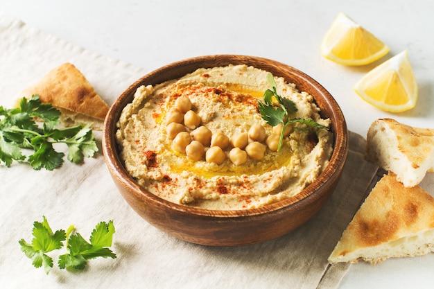 Hummus dip z ciecierzycy, pita i pietruszką w drewnianym talerzu na białym tle