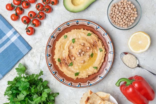 Hummus do brązowej płytki glinianej z niebieskim wzorem. na białym stole znajdują się warzywa, warzywa, trójkątne kawałki pity. widok z góry. leżał płasko.