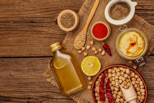 Hummus na starym drewnianym stole. wytrawna ciecierzyca, oliwa z oliwek, cytryna, kminek i papryczka chili