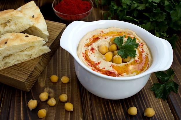 Hummus w białym talerzu na podłoże drewniane