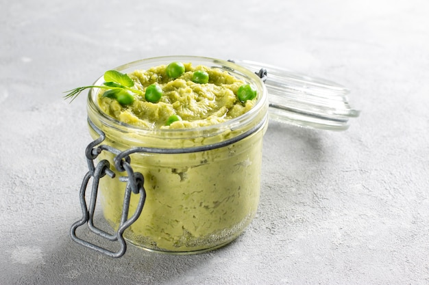 Hummus z awokado w szklanym słoiku z ciecierzycą, zielonym groszkiem, przyprawami na szarym tle
