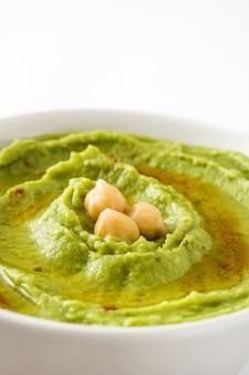 Hummus z awokado z ciecierzycą w misce na białym tle