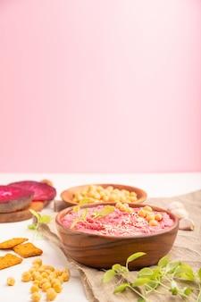 Hummus z burakiem i bazylią mikrozieloną kiełkuje w drewnianej misce na białym i różowym tle.