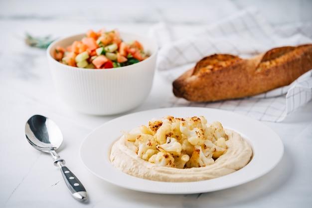 Hummus z kalafiorem, sałatką z pomidorów i ogórków, pieczywo. danie z bliskiego wschodu