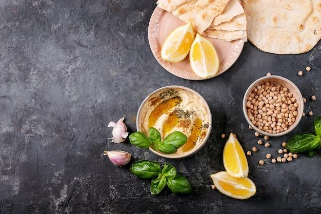 Hummus z oliwą, pitą i mielonym kminkiem w ceramicznej misce, podawany z cytryną, bazylią i ciecierzycą na ciemnej powierzchni. widok z góry, płaski układ
