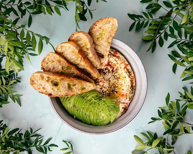 Hummus z plastrami awokado i grzankami
