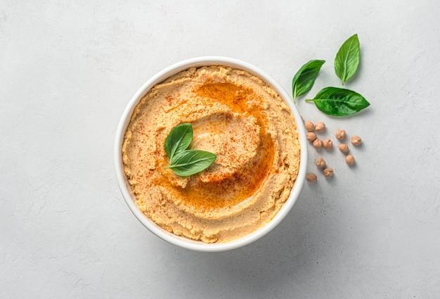 Hummus z przyprawami oliwy z oliwek i bazylią na jasnoszarym tle