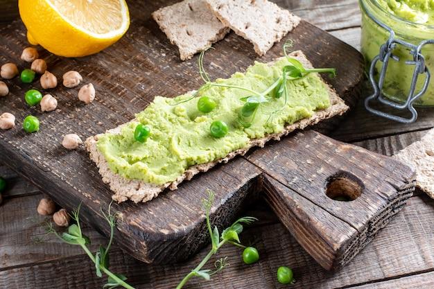 Hummus z zieloną pietruszką z ciecierzycą, zielonym groszkiem i domową ciecierzycą na drewnianym stole