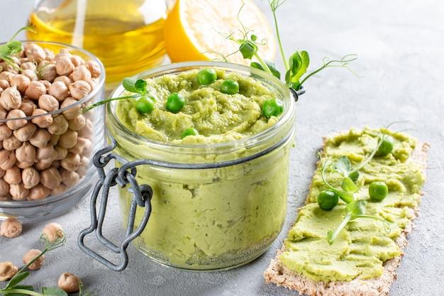 Hummus z zieloną pietruszką z ciecierzycą, zielonym groszkiem i domową ciecierzycą na stole