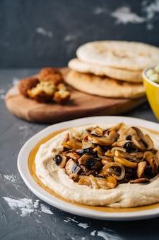 Hummus ze smażonym hummusem ze smażonymi grzybami, surówką z ogórka i pomidora, falafelem i pitą.