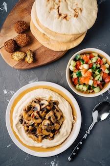 Hummus ze smażonymi grzybami, sałatką z ogórka i pomidora, falafelem i pitą