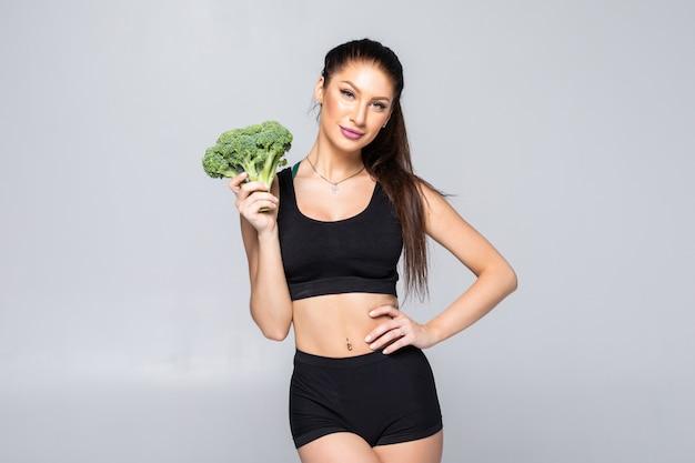 Humorystyczny koncepcja odżywiania: szczupła, zdrowa i sprawna młoda kobieta z brokułami na białym tle