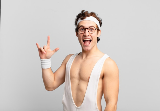 Humorystyczny sportowiec czuje się szczęśliwy, zabawny, pewny siebie, pozytywny i buntowniczy, wykonując ręką rockowy lub heavy metalowy znak