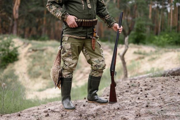 Hunter in rubber boots shells on belt bird hunt.