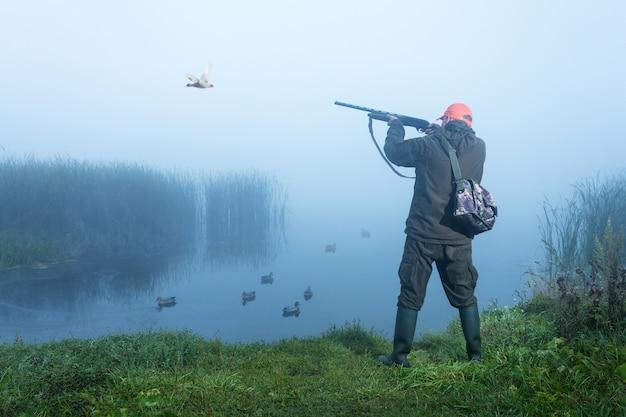 Hunter strzelanie do nieba podczas polowania na kaczki w jesienny poranek. polowanie z wabikiem kaczek na jeziorze.