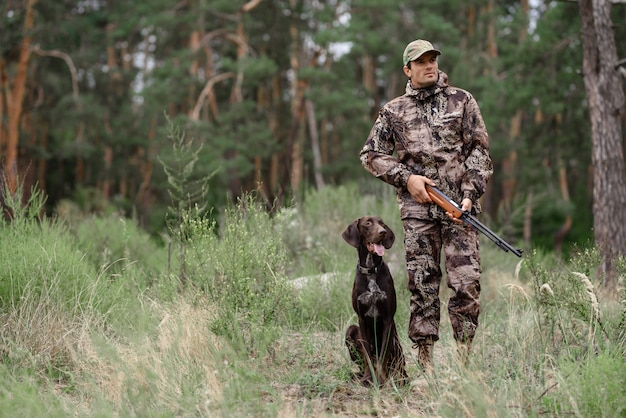 Hunter with rifle walking przez forest pointer dog.