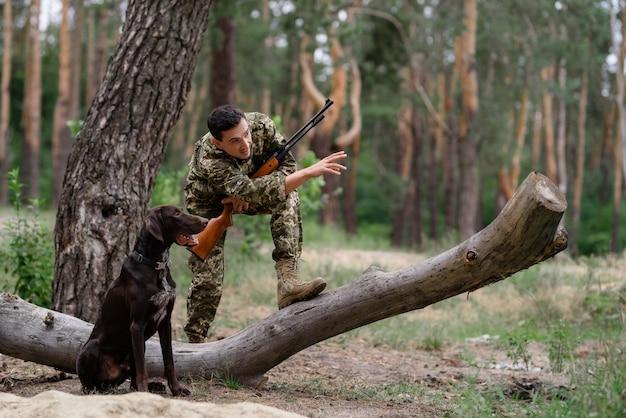Hunter wydaje polecenie psiemu kynologowi podczas polowania.