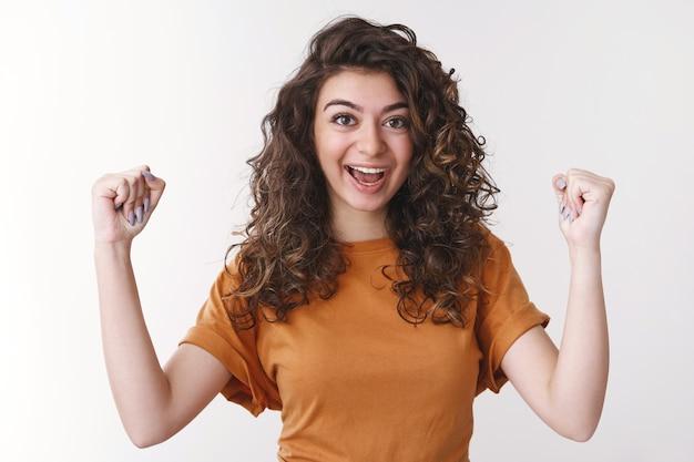 Hurra świetnie. świętując triumf szczęśliwa podekscytowana ormiańska studentka ciesząca się zwycięstwem podnosząca ręce zaciśnięte pięści powiedz tak uśmiechnięta radośnie osiągająca cel, stojąca biała ściana