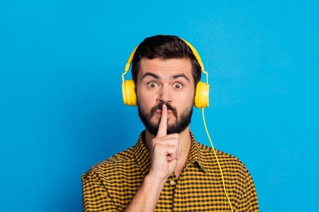Hush my playlist private! śmieszny negatywny facet pokazuje oniemiały symbol usta palec wskazujący nie dziel się sekretem nosić zestaw słuchawkowy w kratkę stylowa modna koszula w kratę na białym tle połysk niebieski kolor