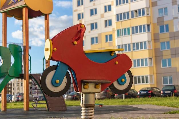Huśtawka dziecięca w formie motocykla. element z placu zabaw na dziedzińcu kamienicy w dzielnicy mieszkalnej miasta.