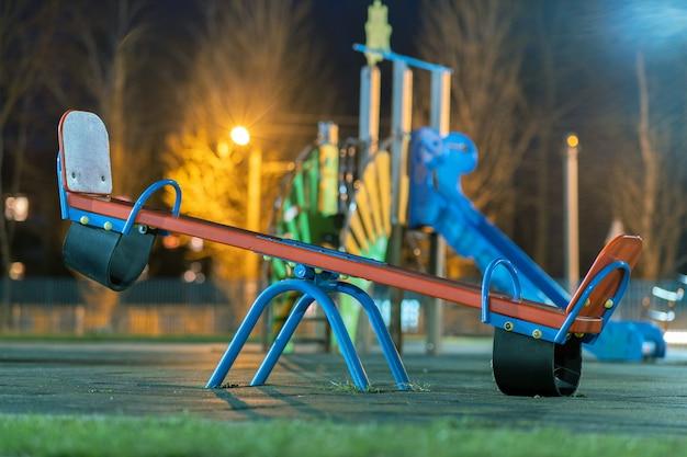 Huśtawka huśtawka na podwórku w przedszkolu z miękką gumową podłogą w nocy.
