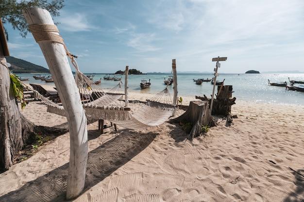 Huśtawka kołyska linowa wisząca na drewnie na plaży z drewnianą łodzią w tropikalnym morzu o poranku