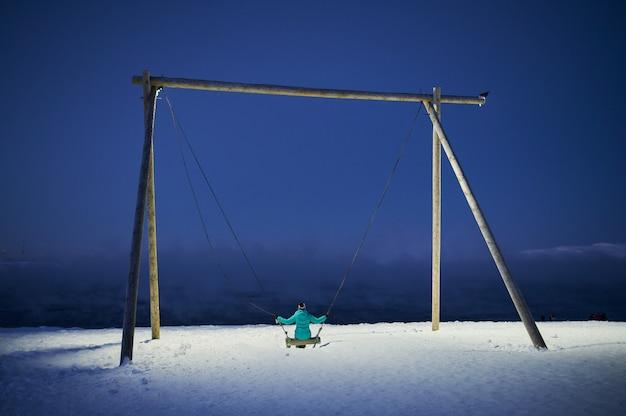 Huśtawka na placu zabaw z grubym śniegiem na ziemi i widokiem na góry i zachmurzone niebo.