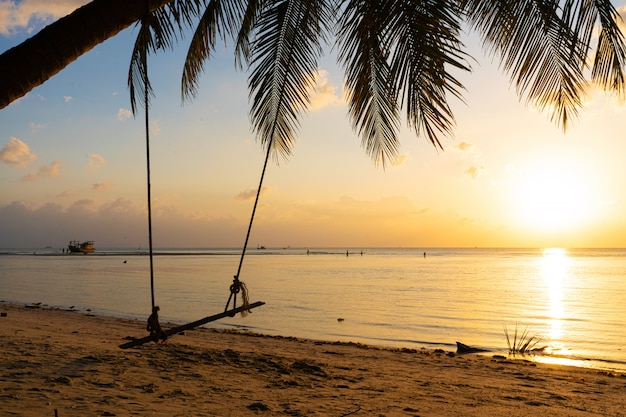 Huśtawka wisi na palmie na tropikalnej piaszczystej plaży nad oceanem. zachód słońca na plaży
