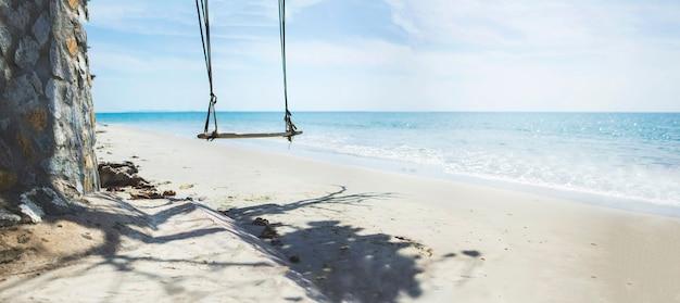 Huśtawki bez ludzi na malowniczej plaży w tropikalnym morzu tajlandii w sezonie letnim ze spokojnymi falami i błękitnym niebem dla relaksu na wakacjach