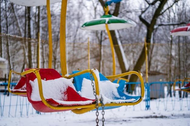 Huśtawki dla dzieci na placu zabaw pokrytym czystym śniegiem w zimowy dzień w parku miejskim na ukrainie