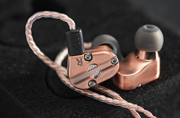 Hybrydowe słuchawki douszne ze zbalansowaną armaturą dynamicznego przetwornika. miedziany metaliczny kolor.